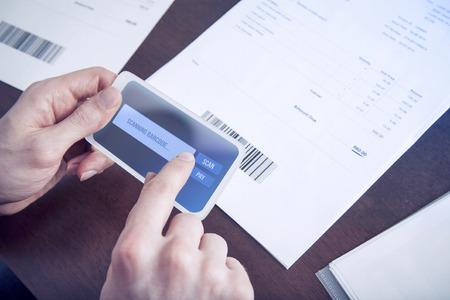Man het betalen van rekeningen met een mobiele telefoon scannen barcode Stockfoto