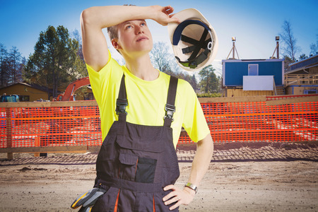 tired worker: Exhausted worker takes helmet of for a break