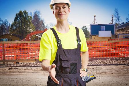 Builder offering handshake at construction site photo