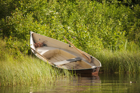 Houten roeiboot op de kust bij bosmeer