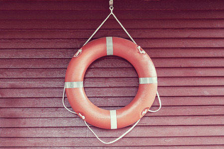 Orange life-buoy hanging on red wooden wall Stock Photo
