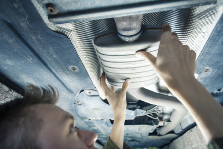 Male mechanic replacing exhaust pipe under car Stockfoto
