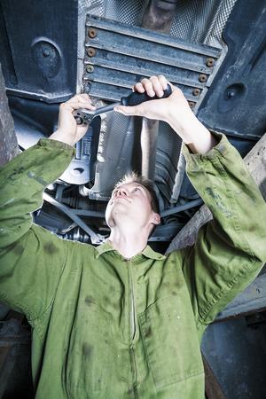 Mechanic tightening with ratchet under car platform photo