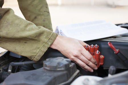 Mechanic reading instructions manual and replacing broken part photo
