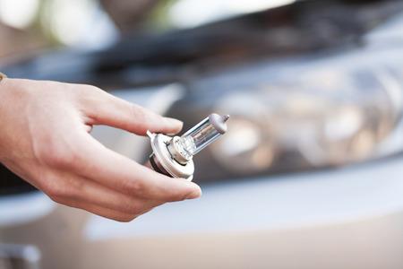 broken car: Mechanic changing headlight bulb