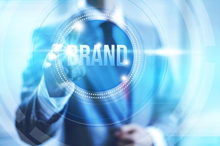 Businessman pointing towards camera selecting brand, virtual interface Stock Photo