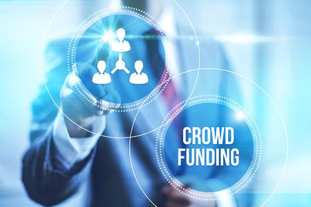 towards: Businessman pointing towards camera selecting crowdfunding , virtual interface