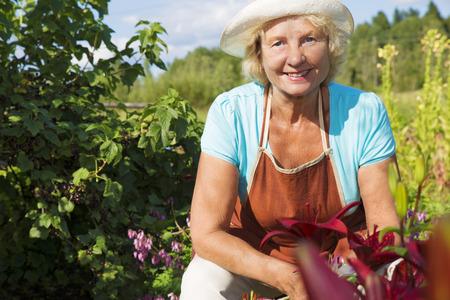 taking a break: Portrait of lovely senior gardener taking a break at the garden at midday Stock Photo