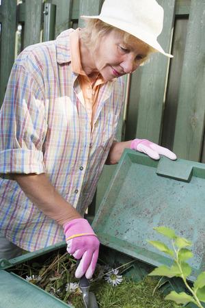 composting: Senior woman gardener composting grass in the garden, holding gardening tool Stock Photo