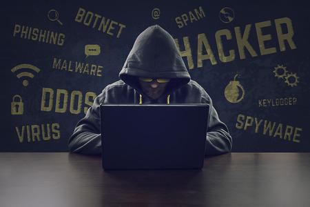 Hooded cyber criminal stealing secrets with laptop Foto de archivo