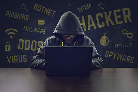 computer hacker: Hooded cyber criminal stealing secrets with laptop Stock Photo