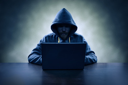 secure data: Hooded computer hacker stealing information with laptop Stock Photo