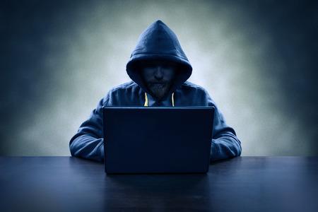 Hooded computer hacker stealing information with laptop Standard-Bild