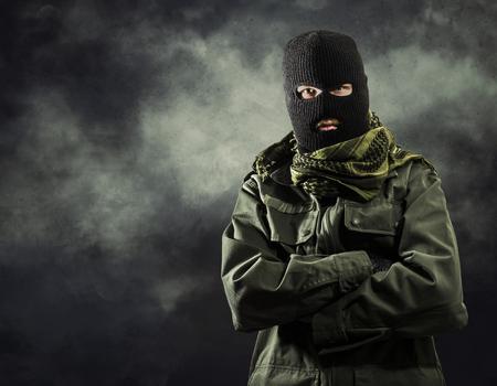 Portrait du terroriste masqué veste militaire avec de la fumée sur fond