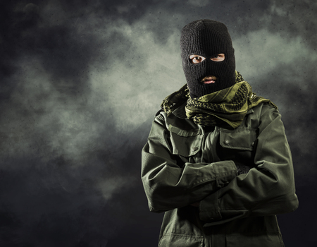 Portrait of masked terrorist in military jacket with smoke on background Stok Fotoğraf