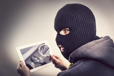 passwords: Masked hacker stealing passwords form mobile device tablet