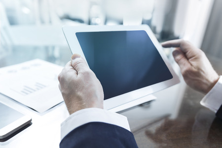 using tablet: Close-up of modern businessman using tablet computer with reflective screen at office Stock Photo