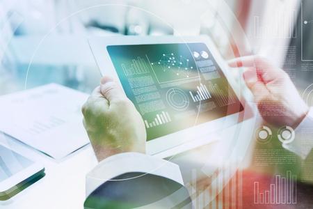 Moderne zakenman die tabletcomputer met behulp van financiële gegevens en grafieken op het scherm