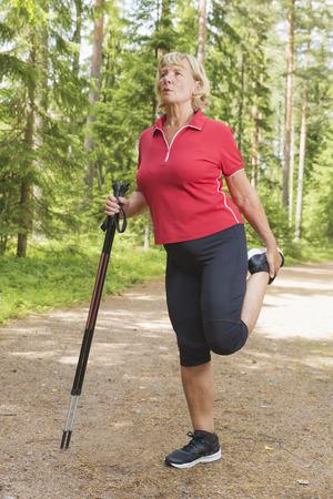 Sportieve oudere vrouw die en het uitrekken zich benen opwarmen die noordse het lopen polen vóór oefening bij een spoor in openlucht houden.