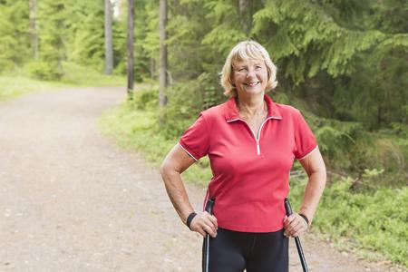 Close-up portret van een lachende senior vrouw, nordic walking door het bos en genieten van een gezonde levensstijl. Stockfoto