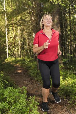 Gelukkige en actieve hogere vrouw die bij dik bos via voetpad lopen.