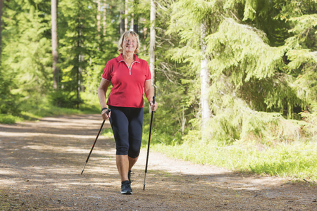 Nordic walking active senior woman working out in the forest and enjoying beautiful summer day.