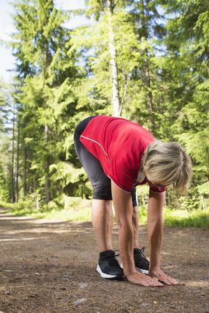 Atletische en flexibele senior vrouw die zich uitstrekt in sportkleding na uitoefening op jogging-track.