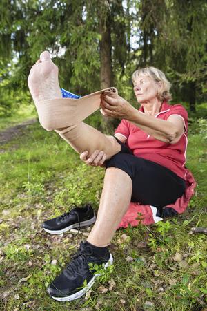 Hogere vrouw die de spanning van de enkelspanning met een verpakkende bandage en een ijspak behandelt. Verticale foto met lage hoek, focus te voet.