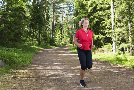 Actieve senior vrouw oefenen. Joggen door het bos op hardloopbaan luisteren muziek op heldere zonnige middag. Stockfoto
