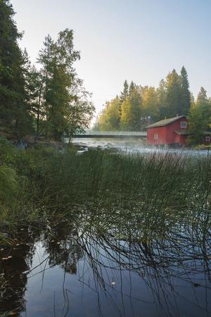 Old wooden mill building and bridge at sunset. Jokela, Kouvola, Finland Stockfoto