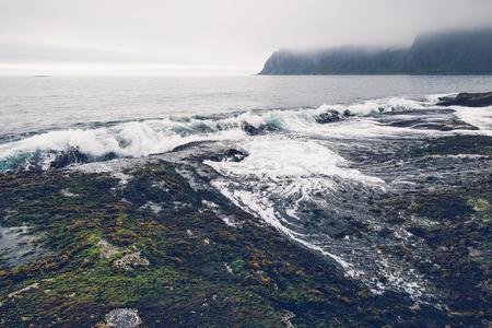 Waves crashing to coast at misty day at Senja island, Norway.
