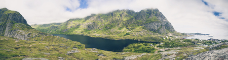 Panoramic view of Ã… i Lofoten, Norway, famous traditional fishing village and popular tourist attraction. Lake between mountains.