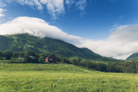 Beautiful Norwegian landscape in Lofoten islands. Red farm buildings, blue sky and high mountains.