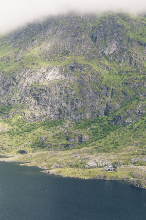 Small house next to lake between huge mountains in Lofoten, Norway.