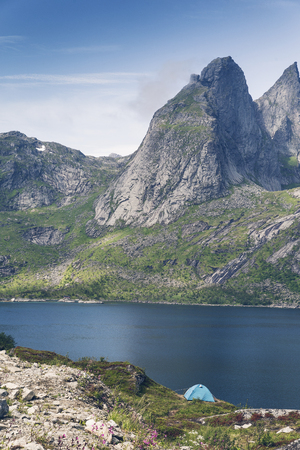 Camping in Lofoten islands, a tent next to fjord and hight mountains at background.
