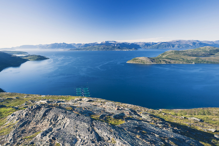 Salmon farms in Norwegian fjord,  near Alta. View from high mountain peak at sunny day.