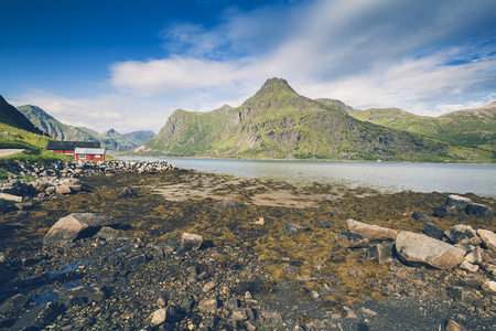 Beautiful Norwegian landscape in Lofoten islands fjord. Countryside farm next to water between hight mountains.