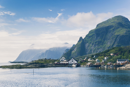 Landscape view of authentic fishing village with yellow rorbu houses in Lofoten Islands, Norway at summer. High mountain peaks and blue ocean. Stockfoto
