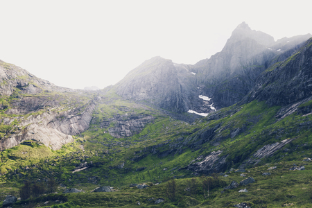 Mountain landscape at summer in Lofoten, Norway. Vibrant image of shadow and light illuminating mountainside.
