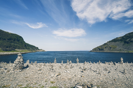 Tourist built pyramid rock formations at fjord shore in North Norway. Blue sky and sunny day.