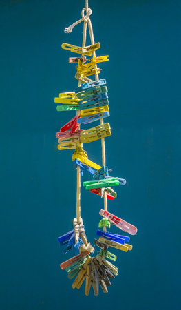 Colorful clothespins are hanging on the cord Stock Photo