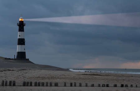 Vuurtoren Breskens lighthouse in the Netherlands shining in the night.