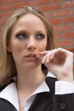 Thoughtful blonde businesswoman with thumb in her mouth photo