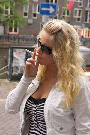 Sexy blonde girl in sunglasses smoking cigarette outdoors