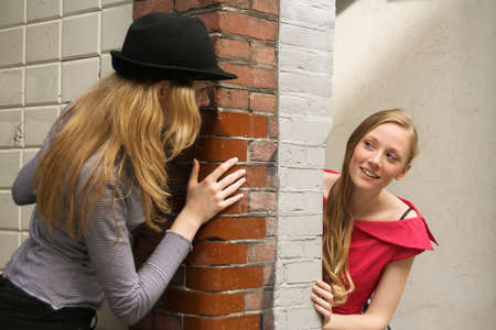 corner house: Two girls peeking around the two sides of the wall at house entrance