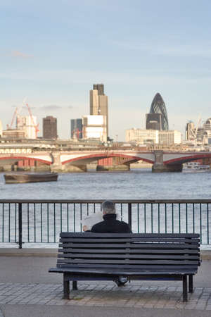 grey haired: Grey haired man sitting on a bench reading newspaper facing London cityscape from a Thames river Southern Bank Stock Photo