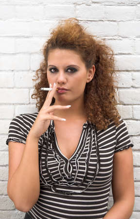 Smoking brunette girl standing next to a brick wall photo