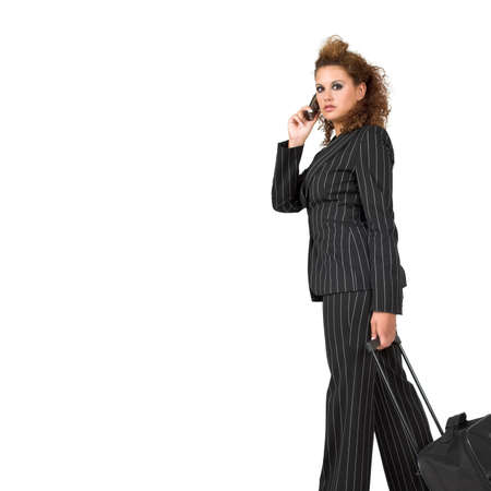 Businesswoman pulling her luggage, isolated on white background; copy space. photo