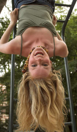 hanging around: Blonde girl hanging upside down in an outdoor playground Stock Photo