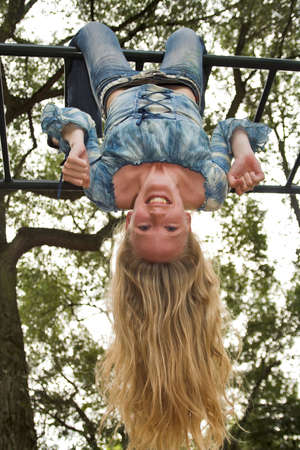 hanging woman: Blonde girl hanging upside down in an outdoor playground Stock Photo